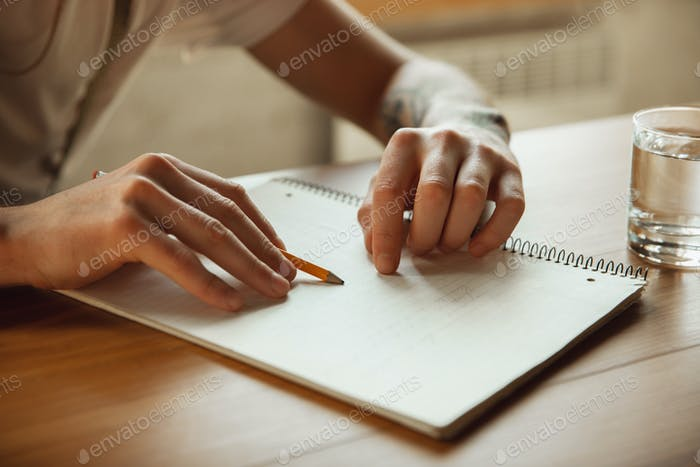 Close up of male hands writing on an empty paper, education and business concept