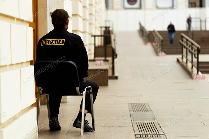 Security guard sitting on a chair at the entrance to the indoor