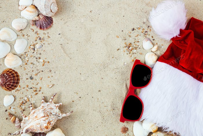 Christmas hat and red sunglasses on the beach. Santa the sand near shells.New year vacation.