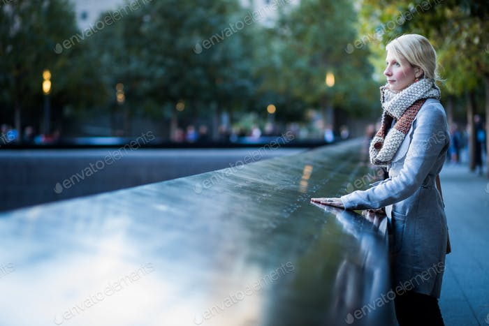 Sad woman looking at the Names of World Trade Center Memorial