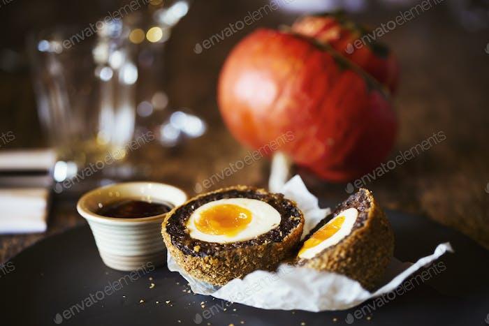 Dorf öffentliche Haus Essen. Ein Gericht mit einem frisch zubereiteten Scotch Ei in zwei Stücke geschnitten und einem Topf mit Soße.