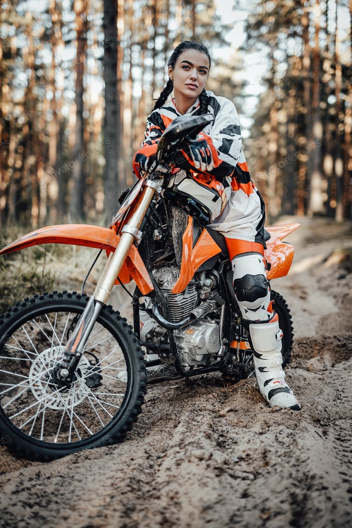 Beautiful young female racer riding motocross bike on a trail of sand in the woods