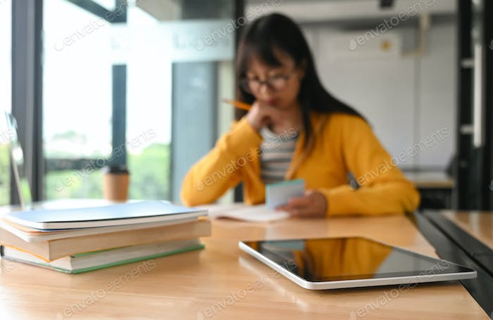 Tablet and many books on the table. Behind the student reading a book.