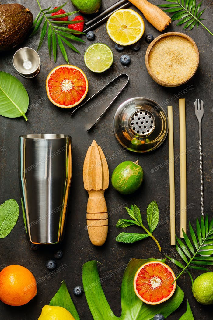 Cocktail making bar tools, shaker, tropical fruits and leaves
