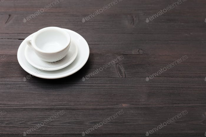 one cup with saucers on dark brown table