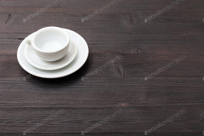eine Tasse mit Untertassen auf dunkelbraunem Tisch