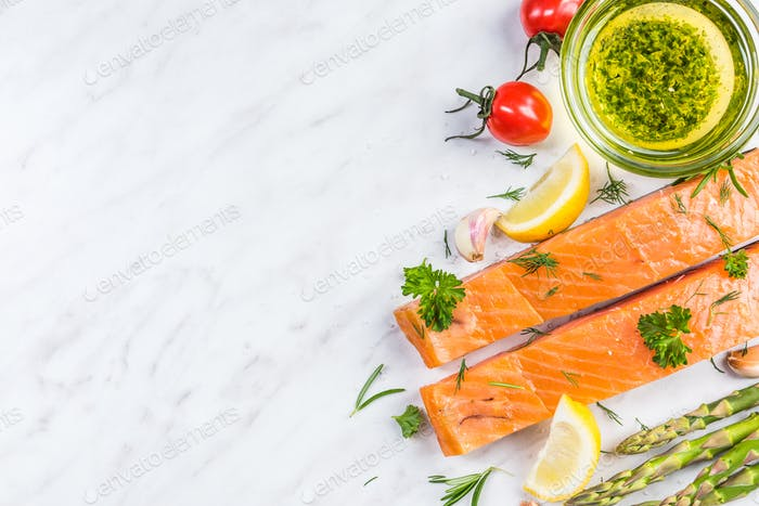 Fresh salmon fillets on white marble table