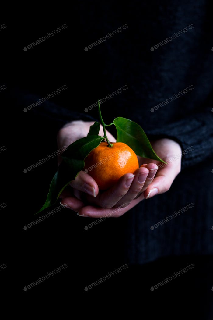 Female Holding Clementine in Hands