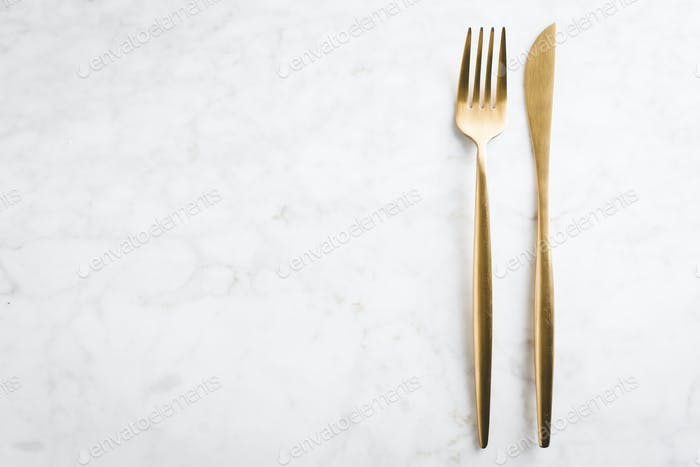 Gold cutlery set on marble background