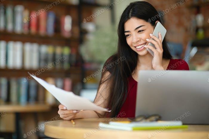 Remote-Geschäft. Asiatische Geschäftsfrau Überprüfen von Dokumenten und Sprechen am Telefon im Café