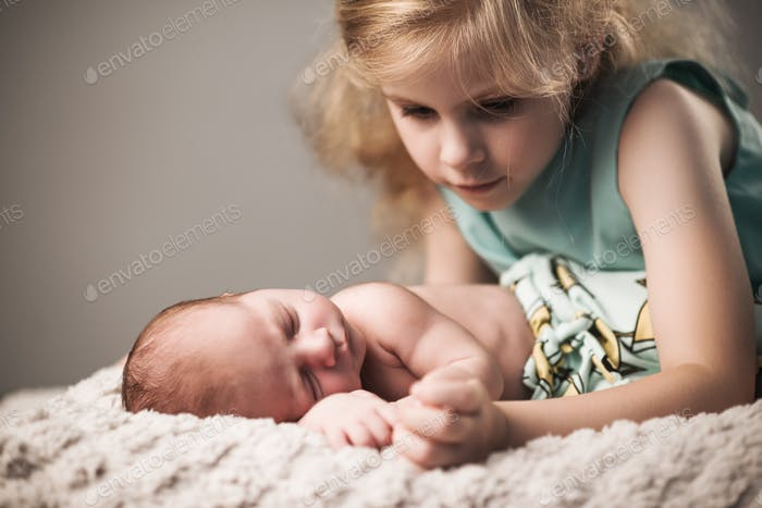 Beautiful little girl in dress looks at brother