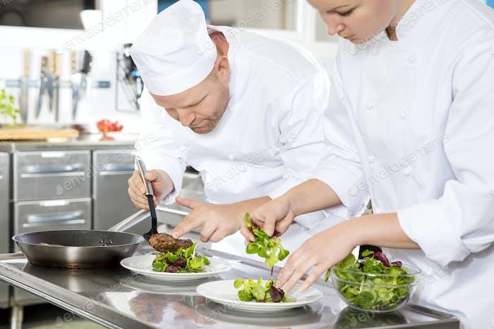 Two chefs prepares steak dish at gourmet restaurant