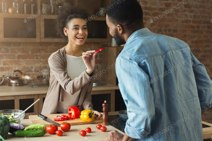Happy black couple cooking healthy food together