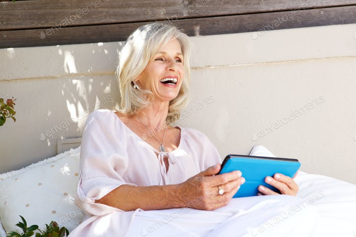 beautiful older woman with tablet laughing outdoors