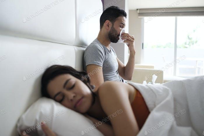 Hombre joven estornudos para frío en cama con pareja