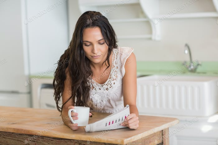Pretty brunette reading newspaper with a mug in the kitchen