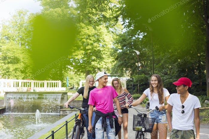 Teenage girls and teenage boys (14-15) walking in park