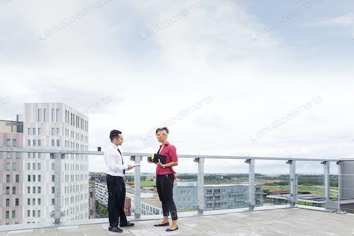 Деловой мужчина и женщина разговаривают на крыше