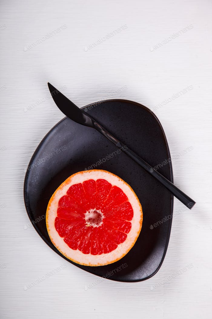 Grapefruit cut in half on a plate with knife