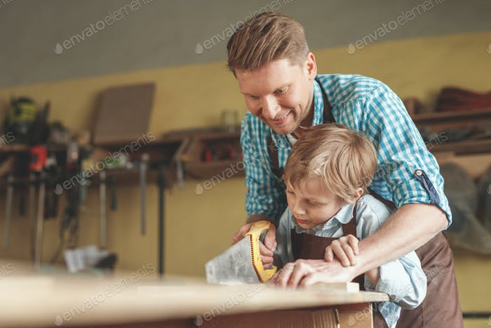 Father and son sawing a board indoors