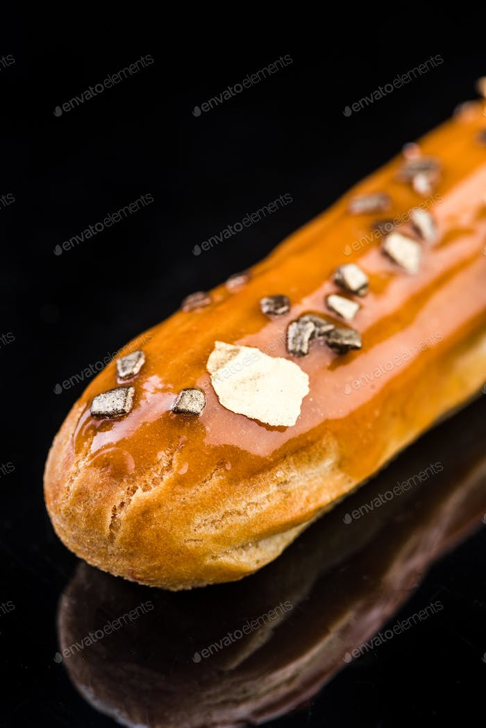 French Artisan Eclair on Black Reflective Background,Copy Space