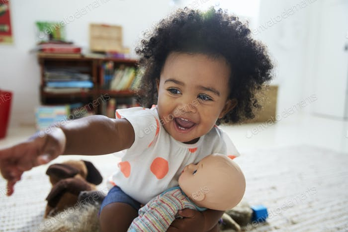 Happy Baby Girl Playing With Doll In Playroom