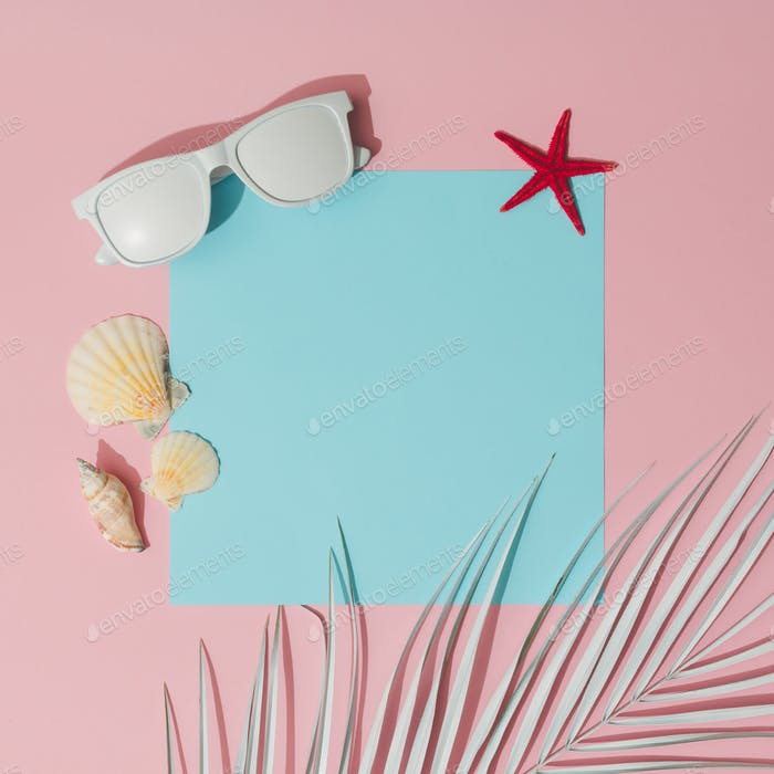 Beach accessories and palm leaves on pastel pink and blue background with copy space.