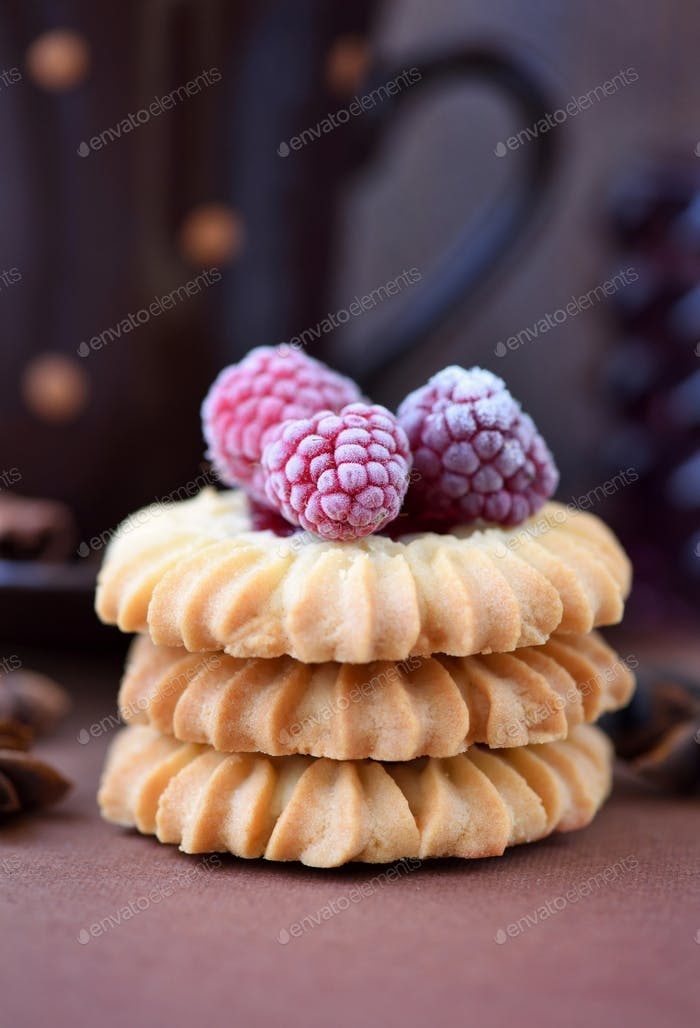 Shortbread cookies with raspberry on brown background