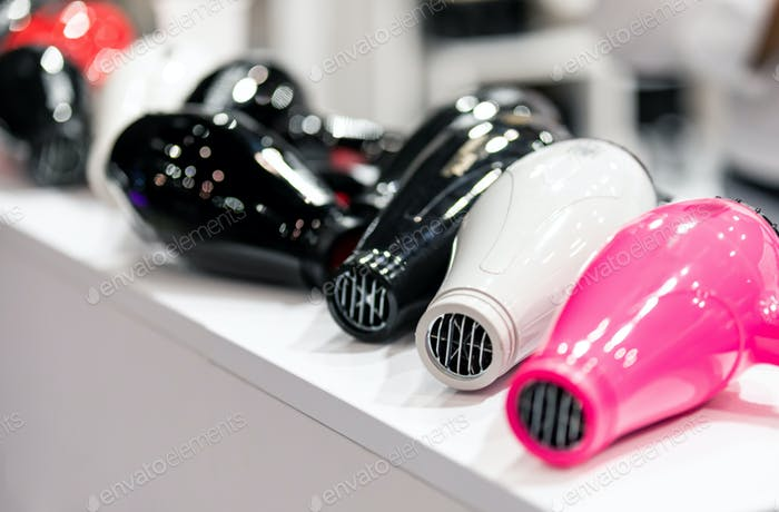 Set of professional hair dryers on shelf in beauty store