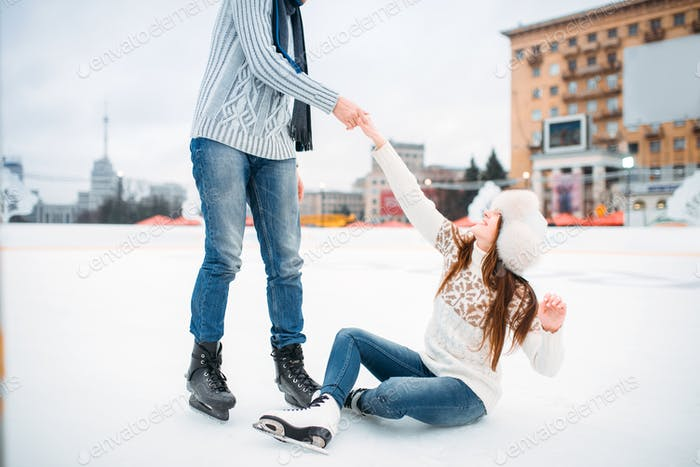 Male person helps a woman to get up, skating rink