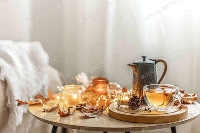 Cozy composition with a cup of tea, a teapot, candles and autumn leaves.