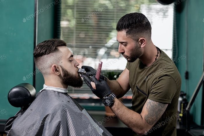 Barber trims mustache of dark-haired stylish man at a barbershop