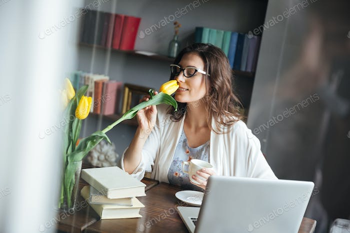 Woman in eyeglasses sitting at table with cup of tea