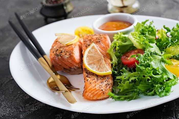 Gebackenes Lachsfilet mit frischem Gemüsesalat. Gesundes Essen. Ketogene/Paleo-Diät.