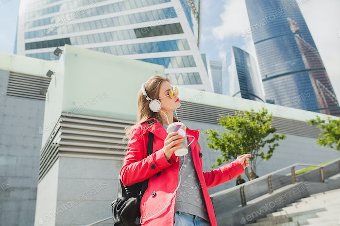 young hipster woman in pink coat, jeans in street with backpack and coffee listening to music