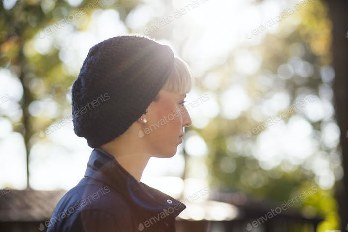 Side view of back lit woman wearing knit hat