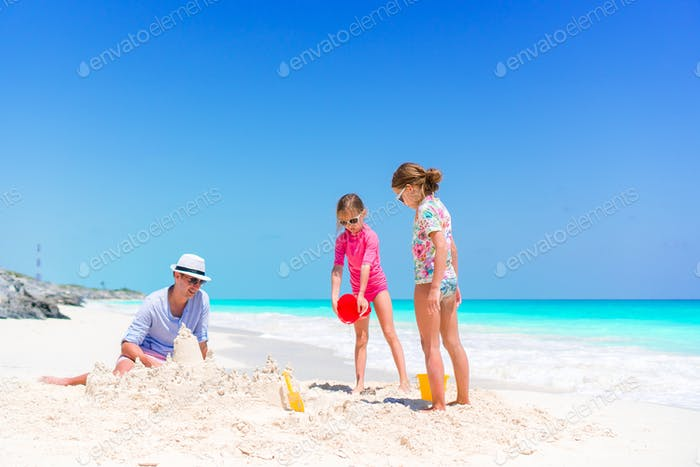 Family making sand castle at tropical white beach. Father and two girls playing with sand on