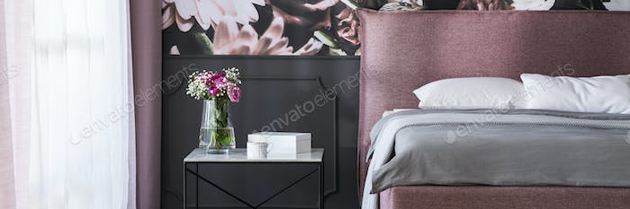 Real photo of marble bedside table with tea cup, box and fresh f