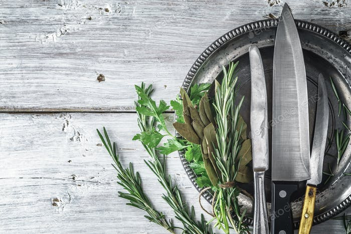Metal plate with knifes and different  herbs on the white table