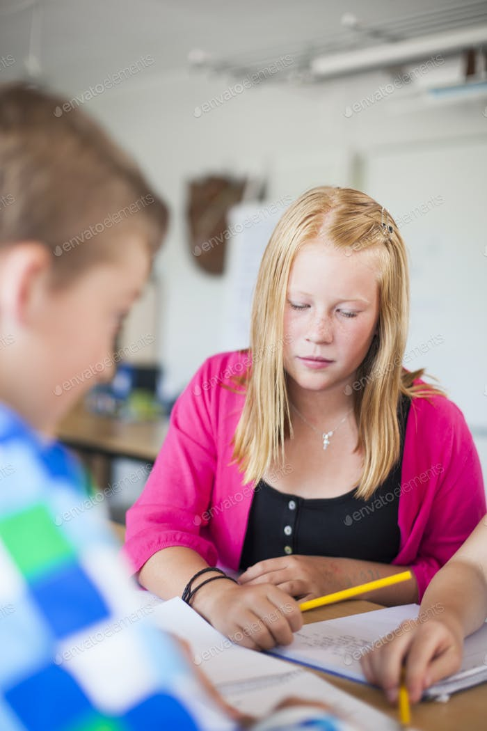 Junior high students studying in classroom