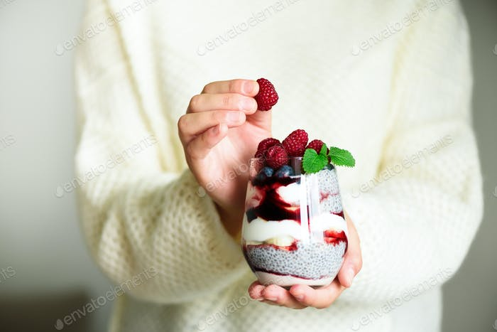 Girl in white sweater holds glass with chia milk dessert, raspberries, blueberries, mint. Healthy