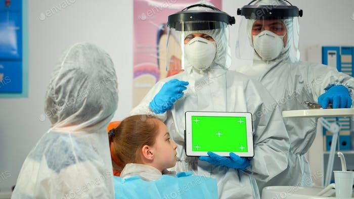 Stomatologe mit Overall zeigt auf Mockup Greenscreen Display