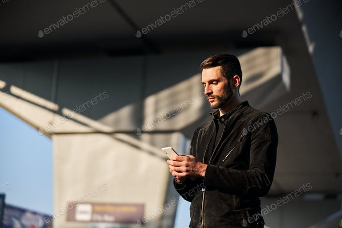 Male smartphone user standing outdoors alone at daytime