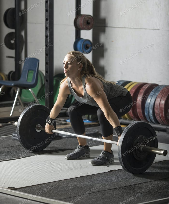 Strong female athlete preparing for heavy lift in grungy gym.