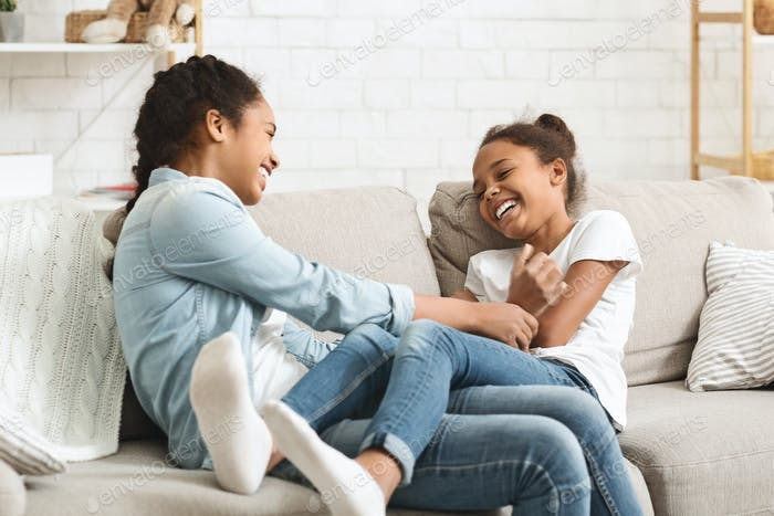 Cute black sisters having fun together at home