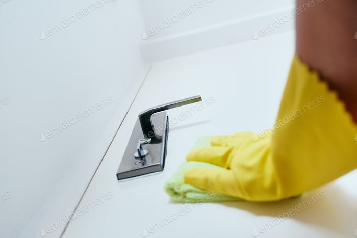 Person Cleaning And Disinfecting Door Handle