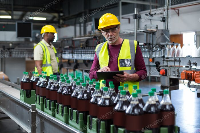 Factory worker with digital tablet monitoring drinks production line