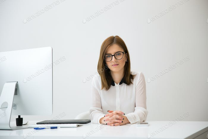 Portrait of a businesswoman sitting at the table in office