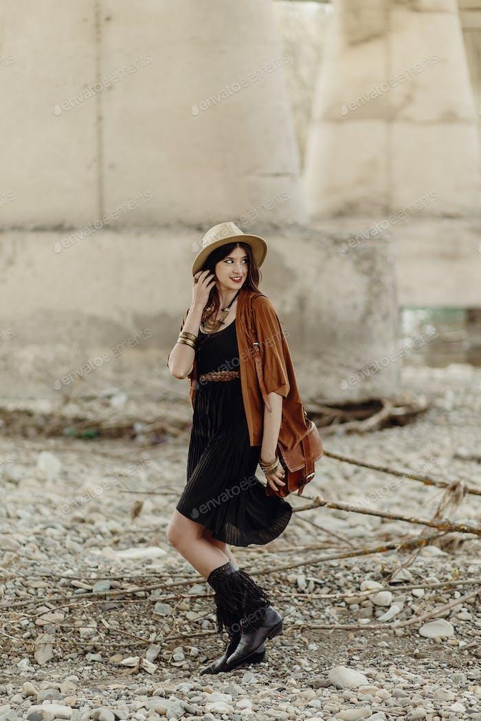 schöne stilvolle Hipster Frau zu Fuß mit Hut, Ledertasche, Fransen Poncho und Stiefel