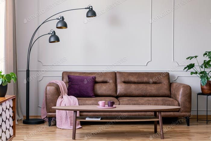 Purple pillow and pastel pink blanket placed on leather couch in
